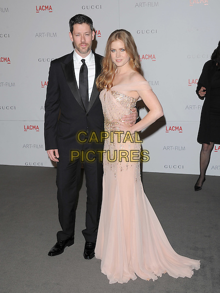 Darren Le Gallo & Amy Adams .The Inaugural Art and Film Gala held at LACMA in Los Angeles, California, USA..November 5th, 2011   .full length black suit pink dress couple hand on hip off the shoulder gold beads beaded                                                                    .CAP/RKE/DVS.©DVS/RockinExposures/Capital Pictures.