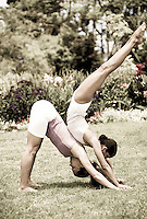 Couple practicing partner yoga in garden setting
