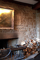 Logs are stacked up beside a stone fireplace protected by a fire guard