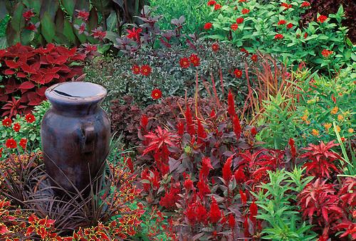 Red garden with ceramic vase fountain overflowing water. Missouri, USA