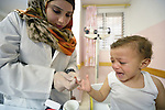 Amani El Assar, a nurse and patient educator, draws a blood sample from a child in a clinic in Shejaiya, a neighborhood of Gaza City that was hard hit by the Israeli military during the 2014 war. The clinic is run by the Department of Service for Palestinian Refugees of the Near East Council of Churches, a member of the ACT Alliance, and funded in part by the Pontifical Mission for Palestine.  This clinic has twice been destroyed by Israeli air strikes, but each time has been rebuilt by DSPR.