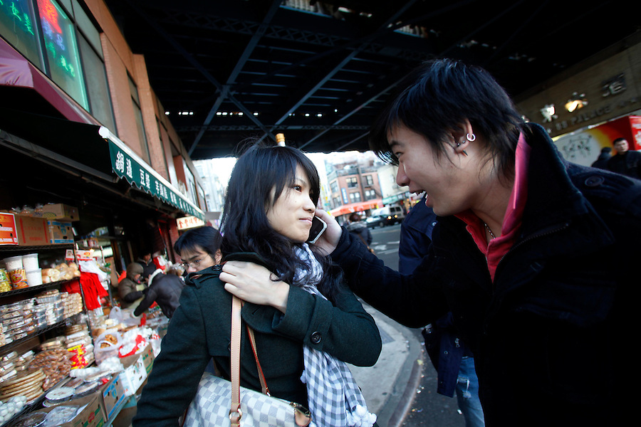 A man lets his girlfriend listen to something on an iPhone in Chinatown in New York City.
