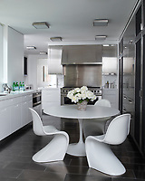 The stylish kitchen features white cabinetry, a stainless steel range oven and polished tiled flooring. An Eero Saarinen table and Verner Panton chairs provide the dining space.