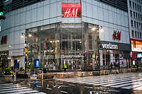 NEW YORK, NY - April 13:  A police officers covers himself of the rain as the H&M store  remains shuttered due to COVID-19 pandemic on April 13, 2020. in New York, United States. The global economy is facing the worst collapse since the WWII, while COVID-19  pandemic has now killed more than 22,000 people in the United States and at least 1,864,629 people died world wide. (Photo by Eduardo MunozAlvarez/VIEWpress)