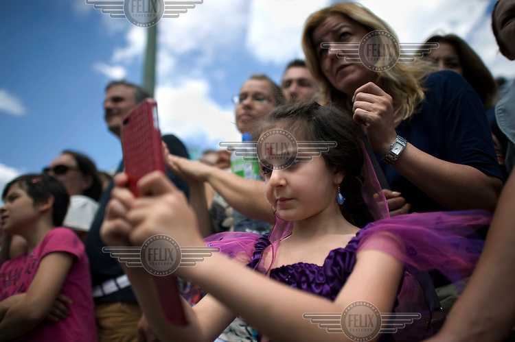 A young girl takes a photograph of the parade on a mobile phone during the Carnival of Cultures (Karneval der Kulturen) in Kreuzberg. The carnival celebrates Berlin's ethnic and cultural diversity.