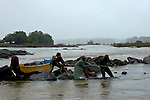 The Marowijne River, Suriname.  Men pull on rope to free boat stuck on a rock in the rapids.
