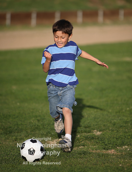 Authentic happy Latino boy playing with soccer ball in field wearing blue striped tee shirt.