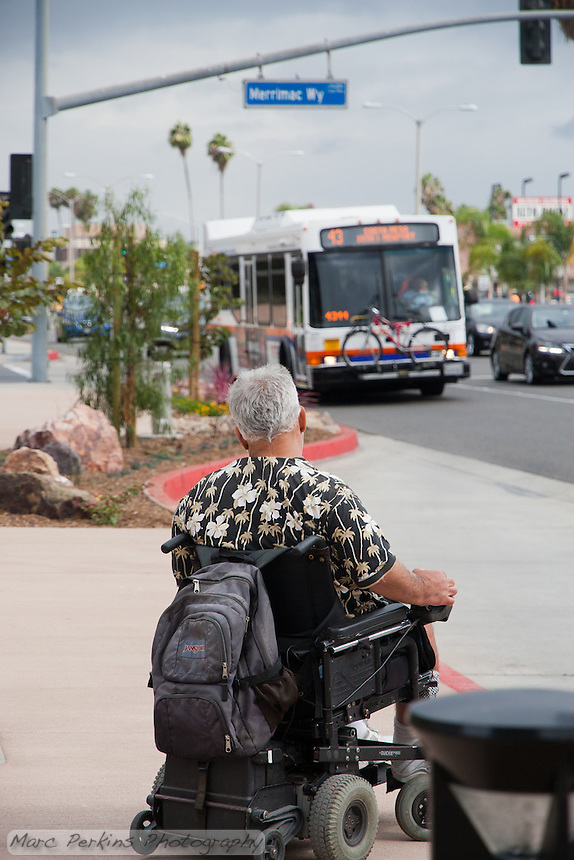 An Orange County Transportation Authority (OCTA) bus pulls into a bus stop to pick up a man in a motorized wheelchair along Harbor Blvd. at Merrimac Way in Costa Mesa, CA.  The day is cloudy, with gray skies, and a stoplight, palm trees, red rocks, and other landscaping can be seen.
