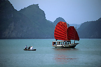 Traditional Vietnamese junk with red sails flying at anchor with four people in a dingy nearby, Halong Bay, Vietnam