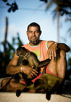 Local fisherman Mildo Hensley sits with his pet howler monkeys during sunset on Little Corn Island in Nicaragua in April, 2009..