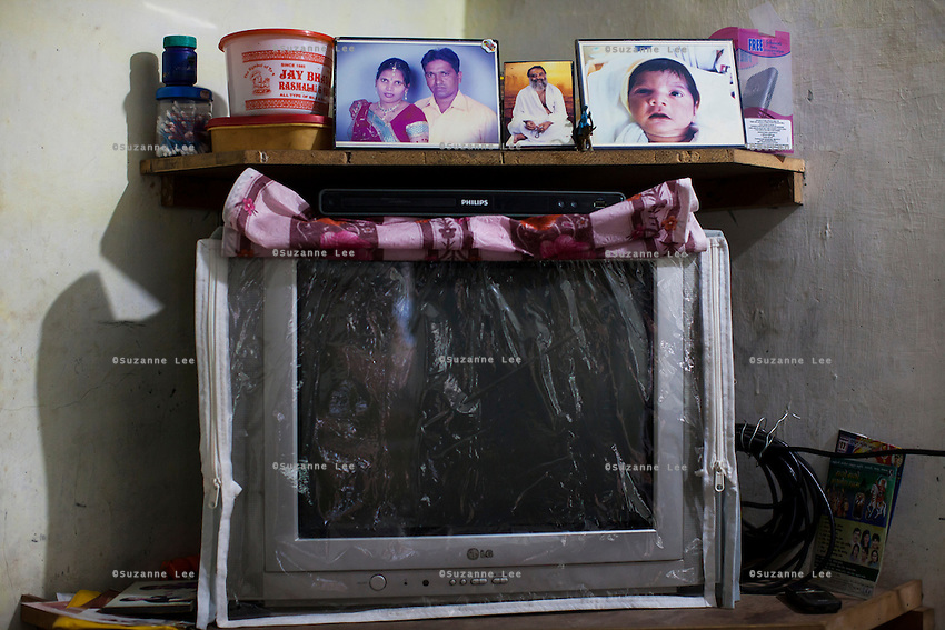 A picture of Sharda Solanki, 36, and her husband Kantibhai Solanki, 38, is displayed next to a picture of a baby boy she carried during one of her 2 surrogacies, in her house in Anand, Gujarat, India on 9th December 2012. While her husband Kantibhai works as a security guard earning 5000 rupees per month, Sharda had made hundreds of thousands with 2 surrogacies that she did with Akanksha Clinic, which she used to buy land, buffaloes, build washrooms in her house and extend the house. She had also saved a substantial amount to fund her 3 children's educations and make sure that her 2 daughters will find husbands to match their current status. Photo by Suzanne Lee / Marie-Claire France