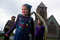 Hannah McHaffie, 9, center, and friends Samantha Dodd, 9, left, and Bernice Hewitt, 7, smile in ront of the Anglican church in Port Stanley, Falkland Islands.