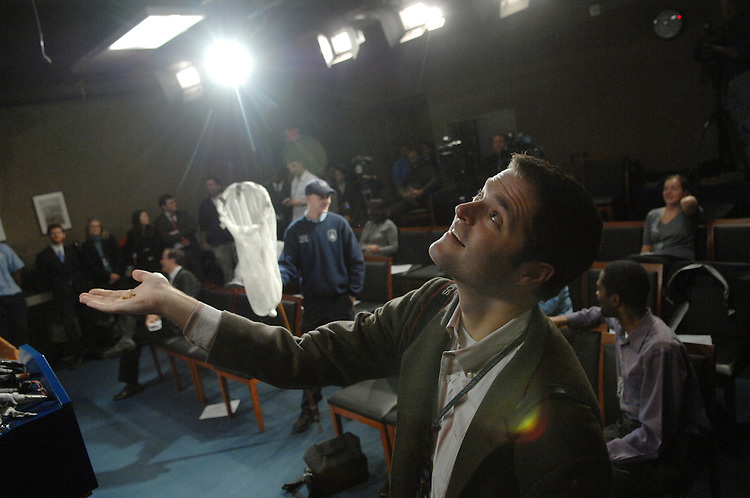 News photographer Mattew Cavanaugh tries to lure, what was believed to be a finch, down from its perch with granola.  The bird was trapped in the Senate Studio before a Sen. Charles Schumer, D-N.Y., news conference. The bird fled to the Daily Press Gallery where it remained at large.