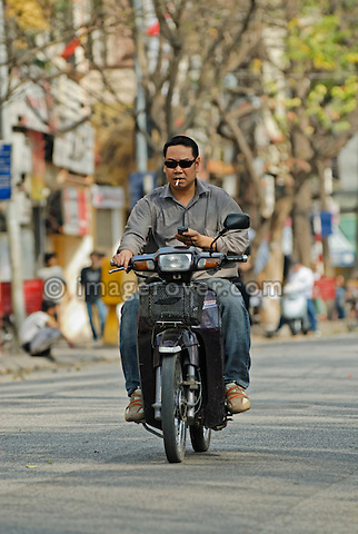 Asia, Vietnam, Hanoi. Hanoi old quarter. Cool vietnamese man, while smoking and using a mobile phone, riding a small motorbike through Hanoi.