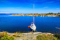 Segelbåt vid Ut-Fredel i Stockholms ytterskärgård med fiskebodar