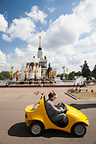 RUSSIA, Moscow. RUSSIA, Moscow. Vistiors riding a yellow car in front of  the Peoples Friendship Fountain at the All-Russia Exhibition Center.