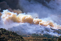 870000379 a los angeles county fire fighting helicopter flies above a burning hillside in the path of the topanga fire in the hills above the san fernando valley in southern california