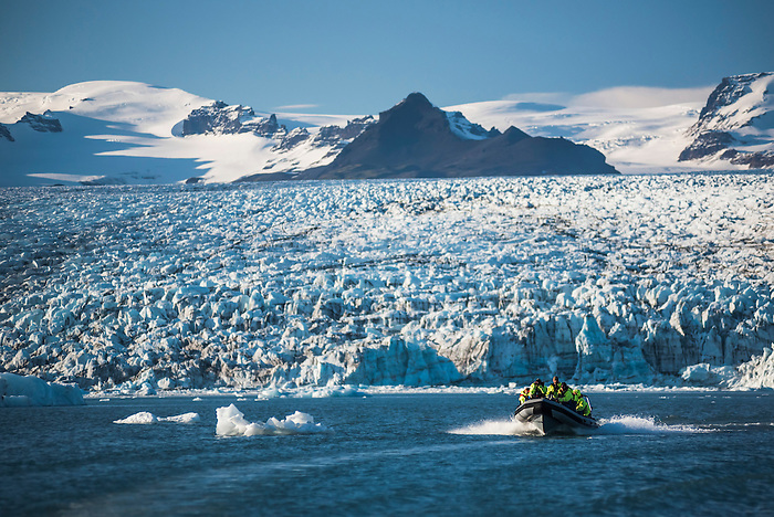 Zodiac boat tour on Jokulsarlon Glacier Lagoon, with Breidamerkurjokull Glacier and Vatnajokull Ice Cap behind, South East Iceland
