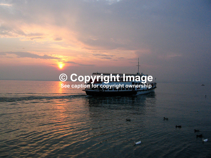 Ferry boat on Lake Garda, Italy, at sunset, 200609190280..Copyright Image from Victor Patterson, 54 Dorchester Park, Belfast, UK, BT9 6RJ..Tel: +44 28 9066 1296.Mob: +44 7802 353836.Voicemail +44 20 8816 7153.Skype: victorpattersonbelfast.Email: victorpatterson@mac.com.Email: victorpatterson@ireland.com (back-up)..IMPORTANT: If you wish to use this image or any other of my images please go to www.victorpatterson.com and click on the Terms & Conditions. Then contact me by email or phone with the reference number(s) of the image(s) concerned.