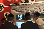Orthodox Jewish men watch Adolph Hitler on a film about Nazi Germany, in 'Yad Vashem' holocaust memorial site in Jerusalem.