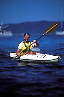 Male sea kayaker with waterproof camera case on deck.  Yachts and sailboats in background. Cypress Island, San Juan Islands, Washington