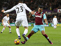 Gylifi Sigurdsson of Swansea City FC is challenged by Dimitri Payet of West Ham United during the Premier League match between Swansea City and West Ham United at The Liberty Stadium, Swansea, Wales, UK. Monday 26 December 2016