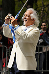 Greek Parade in New York City. An older man in a white suit coat and holding a Greek flag, takes photos during the Greek Parade in New York City.