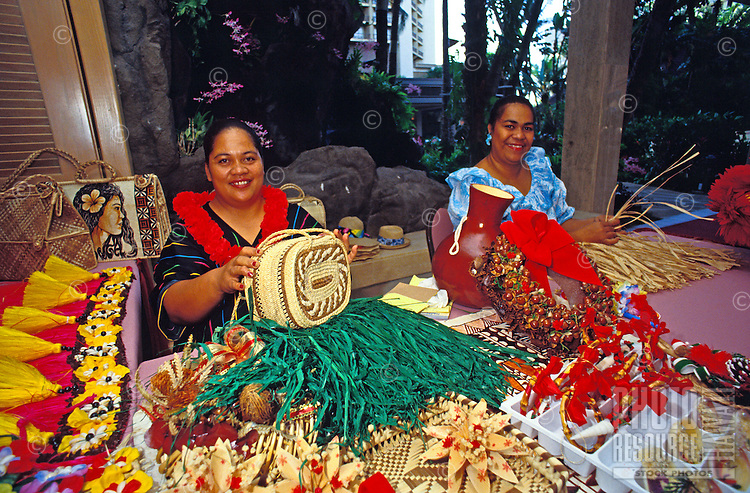 Two Hawaiian women smile while making colorful woven craft items.