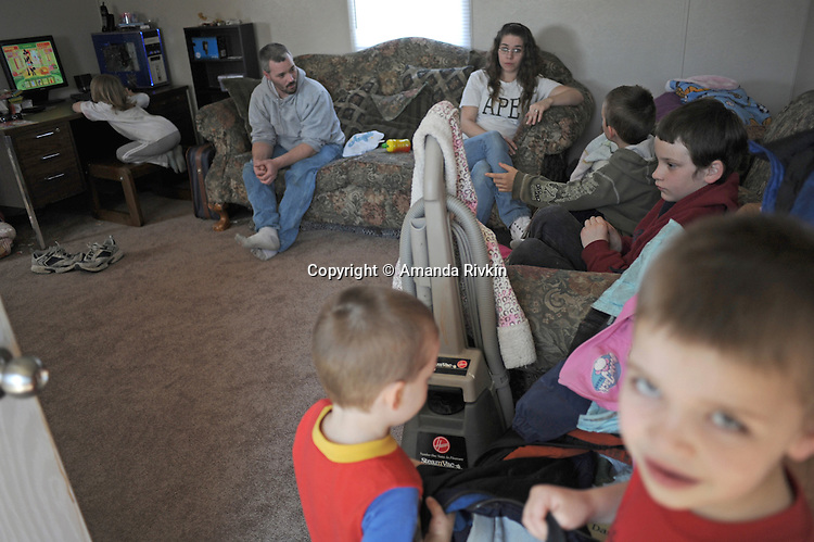 """Terry and Desiree Gonyon with five of their nine children (clockwise from top left) Aedily, 7, Tylar, 7, Michael, 9, Kyle, 6, and Zachary, 3, at home in a self-described combined household """"like the Brady Bunch,"""" after they lost their home in nearby Elkhart, Indiana to foreclosure in the Timber Brook Mobile Home Park in Bristol, Indiana on April 8, 2009.  Two children were in Indianapolis for the day with relatives and friends and the oldest went to live with her mother."""