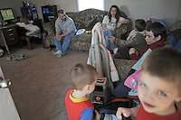 "Terry and Desiree Gonyon with five of their nine children (clockwise from top left) Aedily, 7, Tylar, 7, Michael, 9, Kyle, 6, and Zachary, 3, at home in a self-described combined household ""like the Brady Bunch,"" after they lost their home in nearby Elkhart, Indiana to foreclosure in the Timber Brook Mobile Home Park in Bristol, Indiana on April 8, 2009.  Two children were in Indianapolis for the day with relatives and friends and the oldest went to live with her mother."