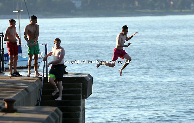 WEATHER PICTURE WALES<br /> Pictured: A boy jumps off the promenade wall in Mumbles, south Wales UK. Tuesday 16 August 2016<br /> Re: High temperatures and sunshine experienced in most of the UK.