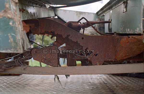 View onto the rotten chassis of the very first 1948 production Land Rover, Chassis No. R860001, Registration HUE 477. Shugborough, UK, 1998. NO RELEASES AVAILABLE. Automotive trademarks are the property of the trademark holder, authorization may be needed for some uses. --- Info: This is the very first 1948 production Land Rover, chassis number R860001. Still in existence, as an unreplacebale part of motor history, but in a very rotten condition it was displayed in 1998 at the Land Rover Series 1 Club event in Shugborough. It was registered with a Warwickshire registration number as HUE 477, giving a hint that it once was a factory vehicle. It was sold in the 50's to a farmer in a small valley. In 1970 it changed hands again for the pricey sum of 15 Pounds. In 1995 it was discovered by a small bunch of Series I buffs but not yet shown to the public.