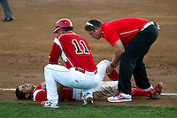 Batavia Muckdogs shortstop Alex Mejia #3 is checked by trainer Mike Petraca as manager Dann Bilardello #11 looks on after Mejia injured his knee while running through first base\during a game against the Staten Island Yankees at Dwyer Stadium on July 30, 2012 in Batavia, New York.  Batavia defeated Staten Island 5-4 in 11 innings.  (Mike Janes/Four Seam Images)