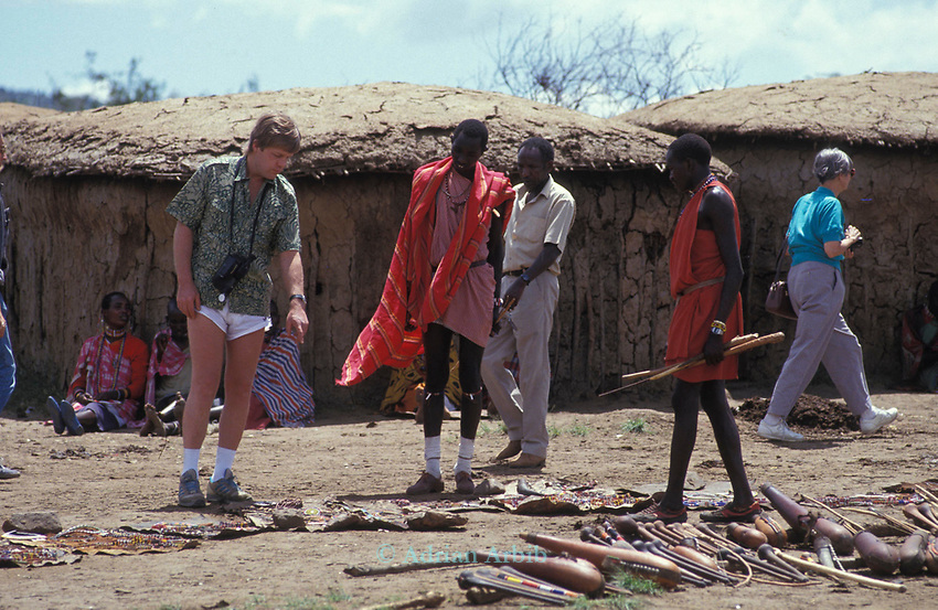 An American tourist haggles with a Maasai woman in a cultural manyatta  set up to interface the Maasai directly with tourists.