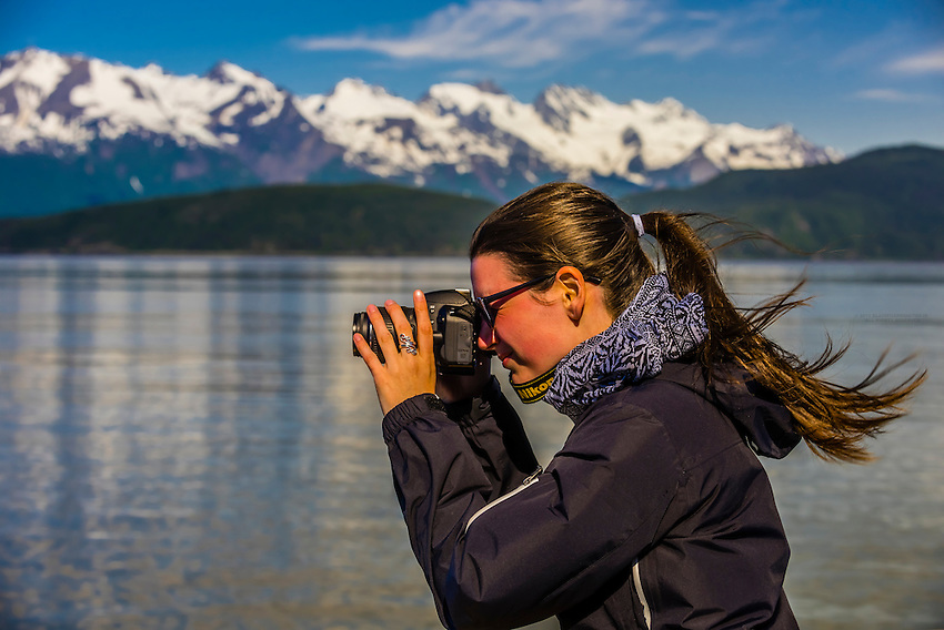 """A tourist aboard the Alaska Fjordlines catamaran """"Fjordland"""" snaps a photo while the ship sails down the Lynn Canal, the deepest fjord in North America, between Haines and Juneau, Inside Passage, Southeast Alaska USA."""