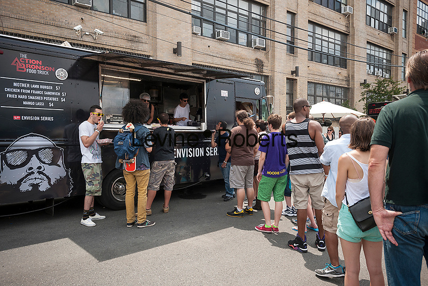 Hipsters line up at the Action Bronson food truck at the annual Bushwick Block Party in the Bushwick neighborhood of Brooklyn on Saturday, July 27, 2013. Young adults came from all over to listen to music and to hang out with their friends and neighbors.  The party took place on Moore Street and was organized by the street's most well know resident, Roberta's Pizza. (© Richard B. Levine)