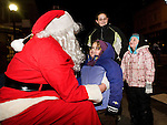 TORRINGTON, CT- 28 November 2014-112814EC01--   Rachel Donovan tells Santa what she wants for Christmas while her sister Allison and mother Indya Holmes looks on. The Coe Memorial Park tree lighting brought hundreds to downtown Torrington Friday night. Mayor Elinor Carbone helped count down to the lighting, then attendees walked down Main Street to see the City Hall Christmas tree lit and hear music from a brass band. Erin Covey Republican-American
