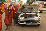 A procession of Buddhist monks make their way to 7th street, annually in November, to receive alms.  Yangon Myanmar (Rangoon Burma) 2008.
