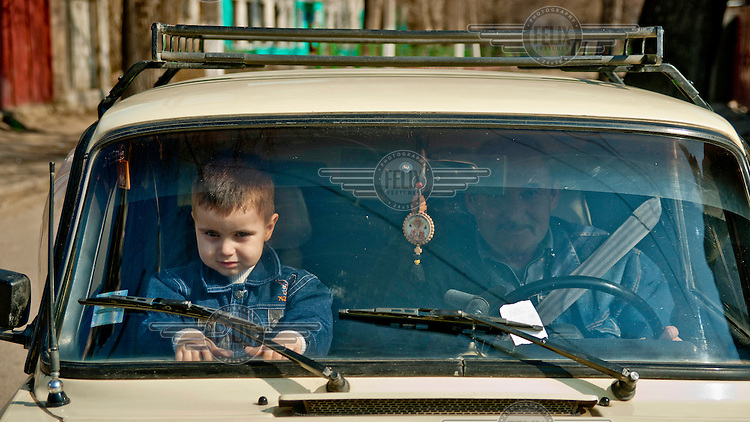 A man and a little boy are seen through the windscreen of their Lada.
