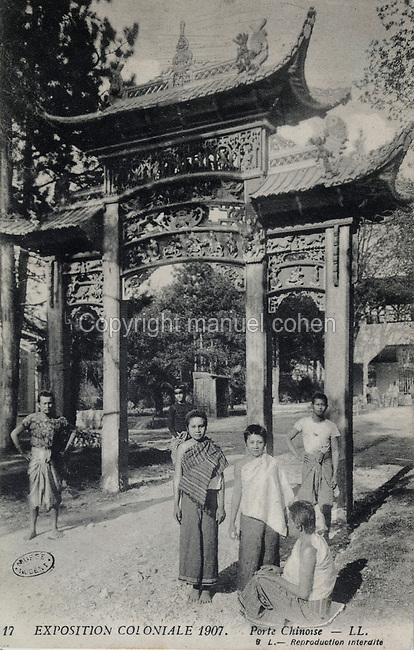 Porte Chinoise or Chinese Gate with Laotian people, at the Colonial Exhibition of 1907, held in the Jardin d'Agronomie Tropicale, or Garden of Tropical Agronomy, in the Bois de Vincennes in the 12th arrondissement of Paris, postcard from the nearby Musee de Nogent sur Marne, France. The garden was first established in 1899 to conduct agronomical experiments on plants of French colonies. In 1907 it was the site of the Colonial Exhibition and many pavilions were built or relocated here. The garden has since become neglected and many structures overgrown, damaged or destroyed, with most of the tropical vegetation disappeared. The site is listed as a historic monument. Picture by Manuel Cohen / Musee de Nogent sur Marne