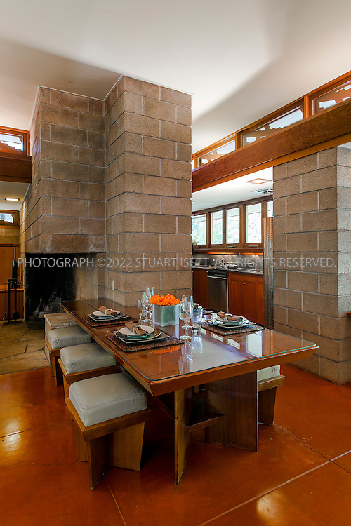 "10/9/2012--Sammamish, WA, USA..VIEW: Interior with dining table and kitchen (back right)..Architect Frank Lloyd Wright planned his ""Usonian"" homes to be affordable for middle-class families. The 1,9500 square foot Brandes home is for sale in Sammamish, Washington (30 minutes from Seattle) at $1.39 million. It features three bedrooms, two bathrooms and a small, separate office/study space...The home was built in 1952, and has redwood trim and Wright's original furniture and some garden sculptures by Wright. It's one of only three Frank Lloyd Wright homes near Seattle...©2012 Stuart Isett. All rights reserved."