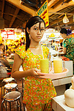 VIETNAM, Saigon, Ben Thanh Market, a  young girl delivers avocado and mango smoothies (sinh to) to people at the market, Ho Chi Minh City