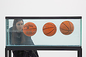 "London, UK. 25 November 2014. A gallery assistant stands next to ""Three Ball Total Equilibrium Tank"" (Two Spalding Shaq Attaq and One Spalding NBA Tip-Off), 1986, by Jeff Koons.  Press preview of the new exhibition Post Pop: East Meets West at the Saatchi Gallery, London. The Tsukanov Family Foundation and Saatchi Gallery present the first comprehensive exhibition examining why Pop Art has had such a powerful influence over artists from world regions that had or still have very different and sometimes opposing ideologies. The exhibition brings together 250 works by 110 renowned artists from China, the Former Soviet Union, Taiwan, the UK and USA in the largest survey to date exploring Pop Art's enduring legacy. The exhibition is open to the public from 26 November 2014 to 23 February 2015, admission is free. Photo: Bettina Strenske"
