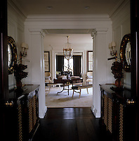 In this tiny hallway dark polished floorboards and antique cabinets form a pleasing contrast with fresh white paint