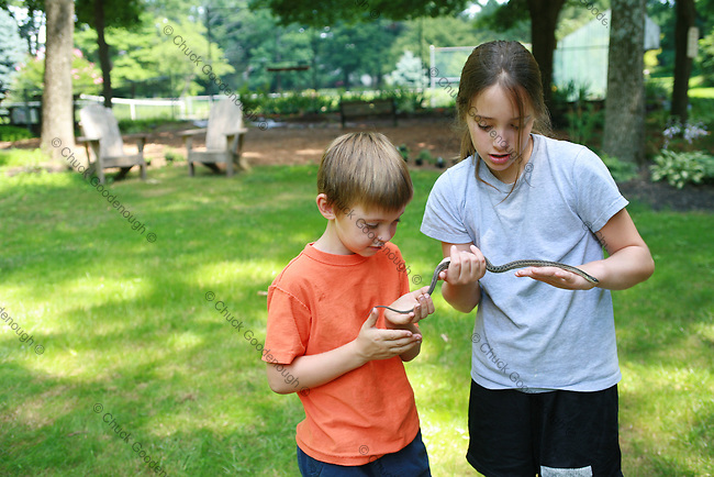 A brother and sister out on the lawn playing with a pet snake