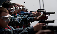 110218-N-DR144-056 ARABIAN SEA (Feb. 18, 2011) Aviation Ordnanceman 3rd Class Marsades Ceasar and other Sailors fire during a 9mm pistol qualification aboard the Nimitz-class aircraft carrier USS Carl Vinson (CVN 70). The Carl Vinson Carrier Strike Group is deployed supporting maritime security operations and theater security cooperation efforts in the U.S. 5th Fleet area of responsibility. (U.S. Navy photo by Mass Communication Specialist 2nd Class James R. Evans / RELEASED)