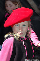 Young girl with a red hat in a maple sugar shack