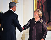 Philanthropist Lin Arison, right, shakes hands with United States President Barack Obama, left, prior to accepting the 2012 National Medal of Arts during the presentation ceremony in the East Room of the White House in Washington, D.C. on Wednesday, July 10, 2013.<br /> Credit: Ron Sachs / CNP