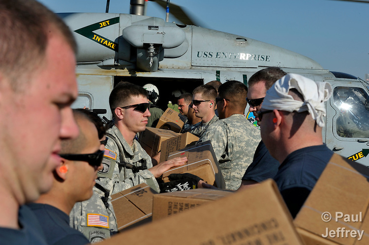 Military personnel from the United States load relief supplies on a U.S. Navy helicopter at the airport in Port-au-Prince, Haiti. The relief supplies, provided by governments and nongovernmental organizations, including the ACT Alliance, were being transported to homeless families in Jacmel, on Haiti's southern coast, who survived their country's January 12 earthquake.