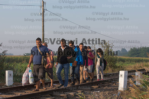 Illegal migrants walk on local railway tracks just after crossing the border between Hungary and Serbia near Roszke (about 174 km South of capital city Budapest), Hungary on August 30, 2015. ATTILA VOLGYI